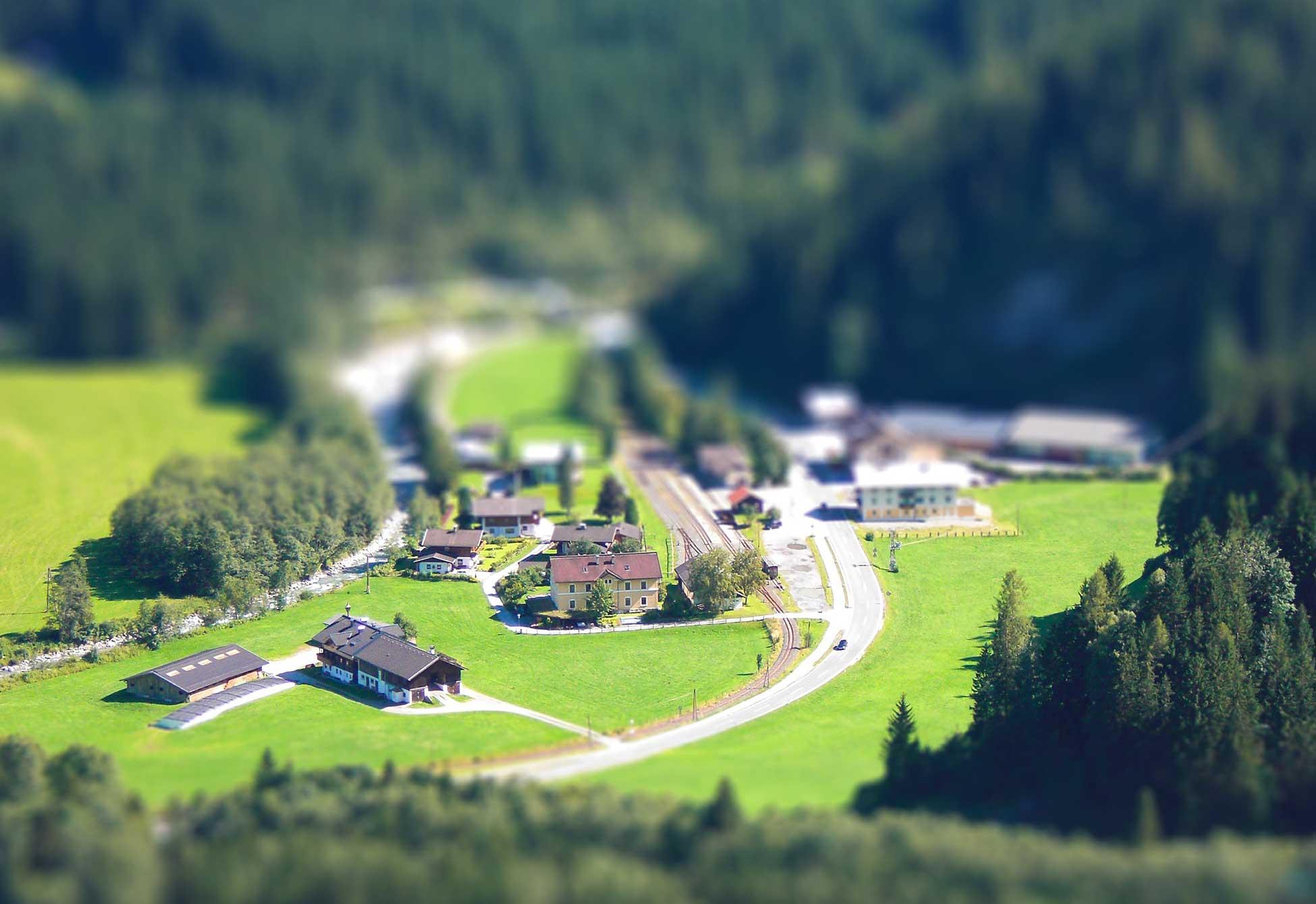 Kleines Bergdorf mit Bauernhof und Bahnhof und umgeben von Wald.